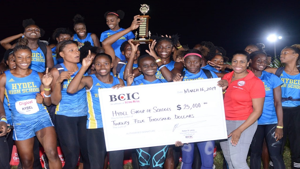 Caption: Hydel High Track & Field team being presented with a trophy and symbolic cheque by Lori- Ann Glasgow- GM, Marketing (BCIC).