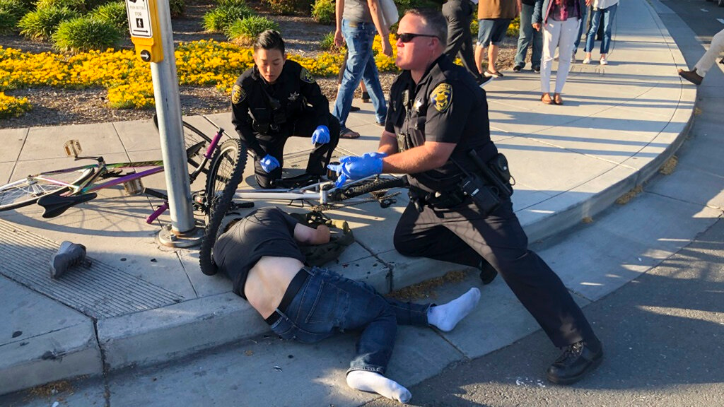 In this photo taken Tuesday, April 23, 2019, provided by Don Draper, a victim of a car crash is offered assistance from police in Sunnyvale, Calif. Draper, a witness to the crash that injured several people, said he was waiting for the light to turn green when a Toyota Corolla plowed through the intersection at high speed. (Don Draper via AP)