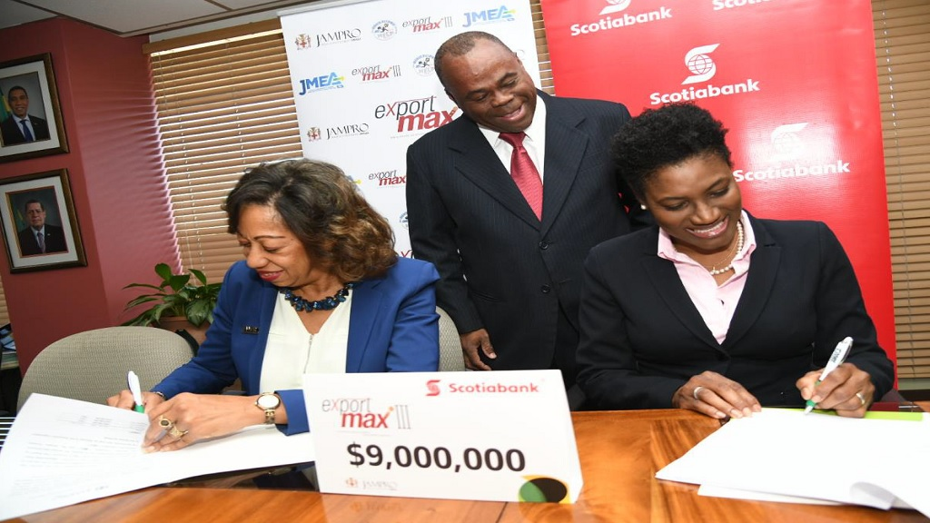 (Seated, L-R) JAMPRO President, Diane Edwards and Audrey Tugwell Henry, EVP, Retail Banking, Caribbean North & Central at Scotiabank happily sign an agreement confirming the banking's J 9 million commitment to JAMPRO, JBDC, and JMEA's export development initiative, Export Max III.  They are joined by Ricardo Durrant, Manager, Sales and Promotion Support Unit at JAMPRO.