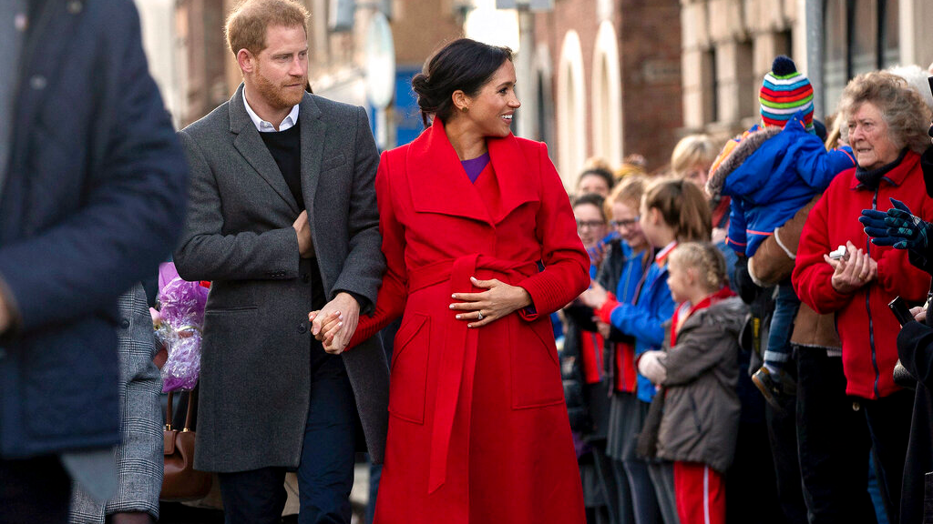 Britain's Prince Harry and Meghan, Duchess of Sussex during a walkabout of Hamilton Square as part of a visit to a new sculpture marking the 100th anniversary of war poet Wilfred Owen's death, in Birkenhead, northwest England, Monday, Jan. 14, 2019. (Charlotte Graham/Pool Photo via AP)