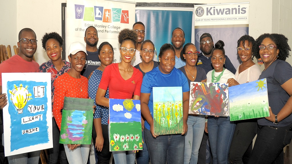 "Members of the Kiwanis Club of Young Professionals, Kingston gathered for a photo to display art works painted by children with autism at the recent staging of the ""Art of Autism"" pilot project held on earlier this month at the Edna Manley College of the Visual and Performing Arts. (Photo: Aston Spaulding)"