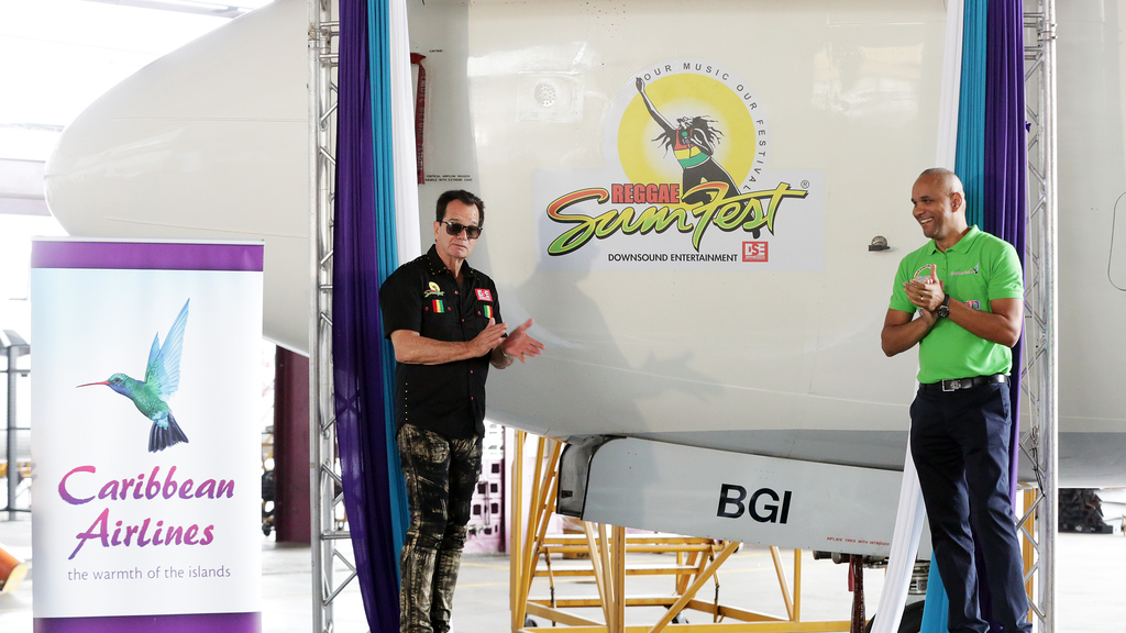 Caribbean Airlines CEO, Garvin Medera (right) and Chairman DownSound Entertainment Limited, Joe Bogdanovich unveil the Reggae Sumfest logo on one of our 737-800 aircraft.