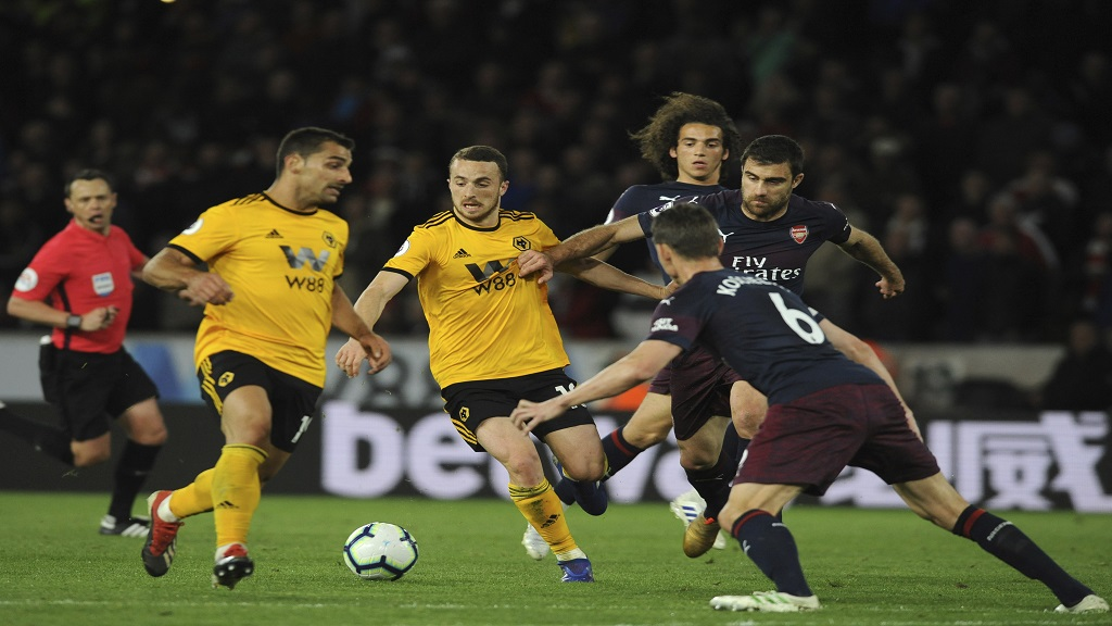 Wolverhampton's Diogo Jota, center, duels for the ball with Arsenal's Sokratis Papastathopoulos, right, during their English Premier League football match at the Molineux Stadium in Wolverhampton, England, Wednesday, April 24, 2019.