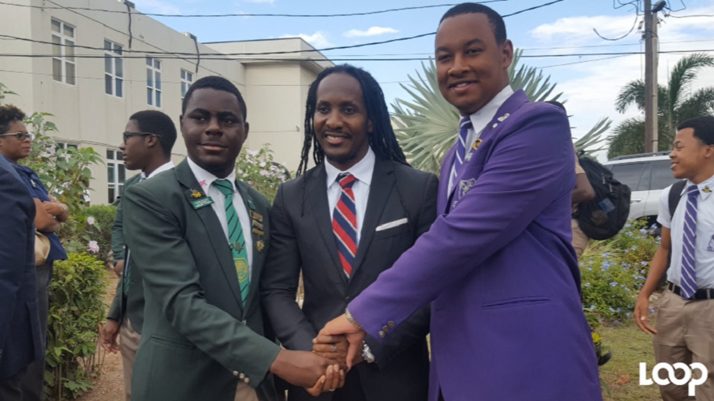Calabar High School Head Boy Andre McKenzie (left) and Kingston College (KC) Head Boy Chad Rattray (right) shake hands after devotion at KC. State Minister in the Ministry of Education, Youth and Information, Alando Terrelonge shares in the occasion.