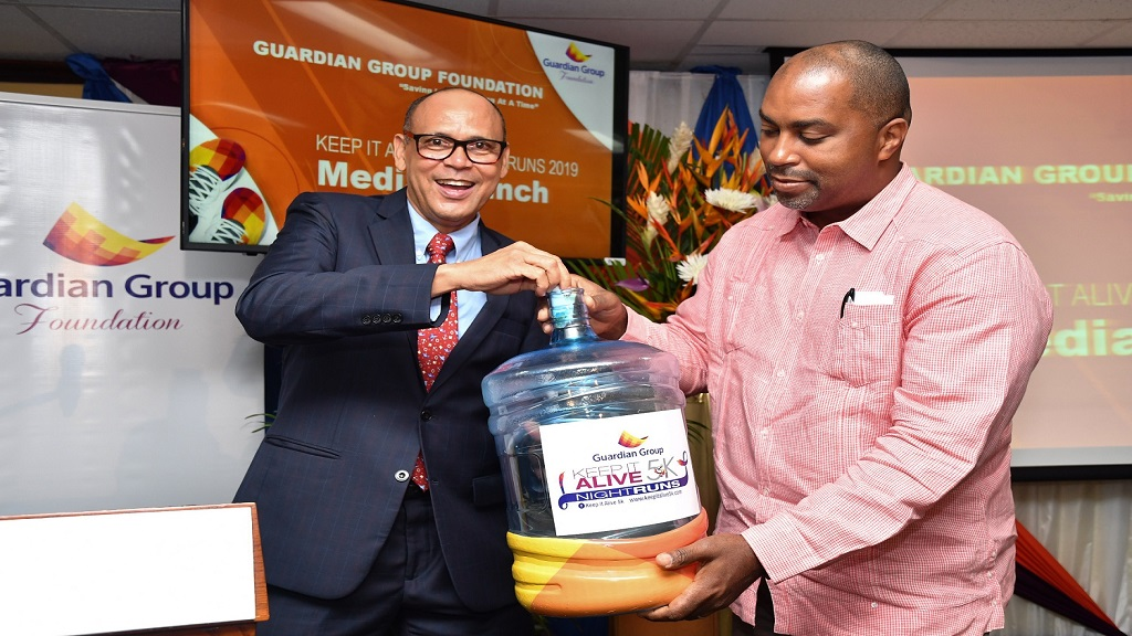 Eric Hosin, President, Guardian Life Limited is joined by Julian Robinson, Member of Parliament, South East St. Andrew in making the first donation towards Guardian Group Foundation Keep It Alive 5k night Run bottle drive. The bottles will be placed at strategic locations including benefitting hospitals and Guardian Life offices, with one hundred percent of the monies collected in the bottles being returned to beneficiaries.