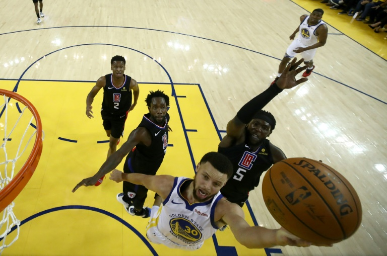 La star des Warriors Stephen Curry évite Montrezl Harrell et monte au lay-up contre les Los Angeles Clippers, le 13 avril 2019 à Oakland