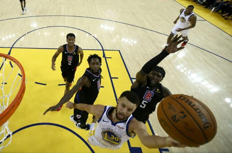 La star des Warriors Stephen Curry évite Montrezl Harrell et monte au lay-up contre les Los Angeles Clippers, le 13 avril 2019 à Oakland