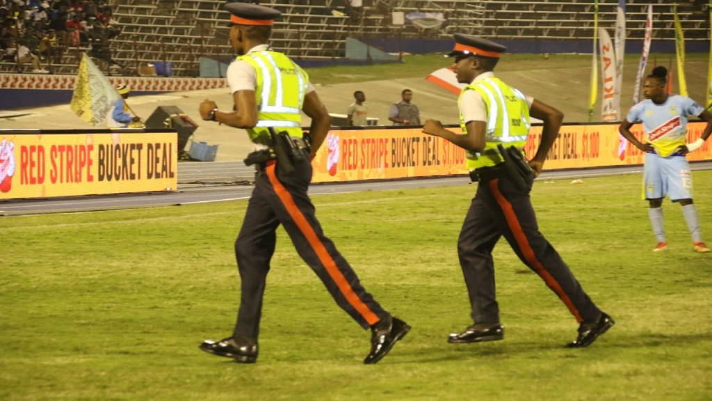 Two police officers make their way on the field following a bottle throwing incident during the RSPL final between Portmore United and Waterhouse at the National Stadium on Monday, April 29, 2019.