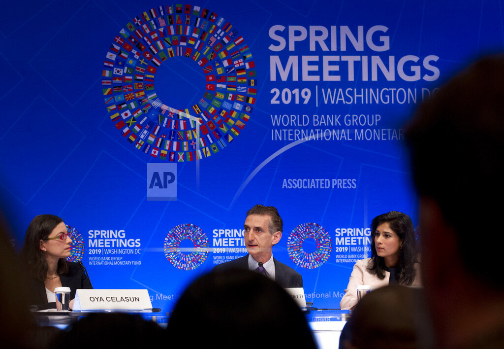 Deputy Director of Research Department at the IMF, Gian Maria Milesi-Ferretti, center, accompanied by Chief Economist and Director of Research Department at the IMF Gita Gopinath, right and Chief of Research Department at the IMF Oya Celasun, left, speaks during a news conference at the World Bank/IMF Spring Meetings, in Washington, Tuesday, April 9, 2019. (AP Photo/Jose Luis Magana)