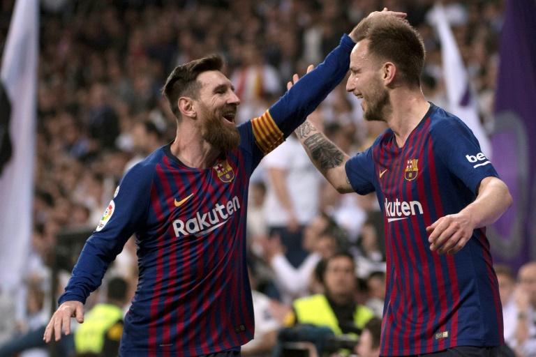 Les joueurs du FC Barcelone Lionel Messi (g) et Ivan Rakitic lors du match face au Real Madrid le 2 mars 2019