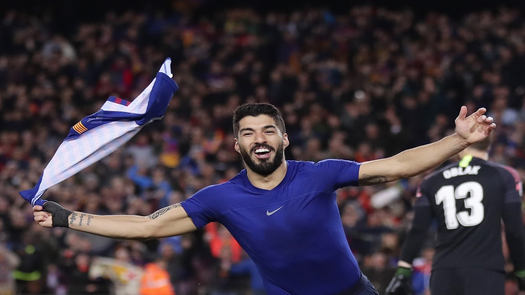 Barcelona forward Luis Suarez waves with his shirt as he celebrates scoring his side's first goal after passing Atletico goalkeeper Jan Oblak, right, during a Spanish La Liga football match at the Camp Nou stadium in Barcelona, Spain, Saturday April 6, 2019.