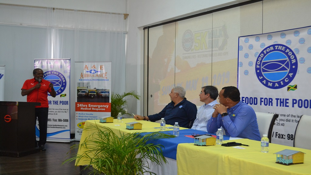 Managing Director of Running Events Jamaica Limited, Alfred 'Frano' Francis speaks during the launch of the fifth staging of the Food For The Poor (FFP) 5K Run/Walk  at the Spanish Court Hotel in Kingston on Tuesday, May 16, 2019. Listening keenly are (from left) FFP executive,  David Mair;  FFP Jamaica Chairman Andrew Mahfood and  Health Minister, Dr. Christopher Tufton.