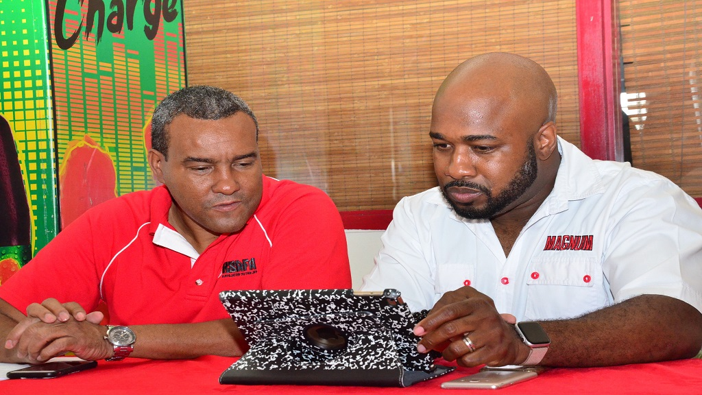 Mark Telfer (right), Brand Manager Magnum, in discussion with Wayne Shaw, President, KSAFA at a press conference at Scotiabank Sports Club, Liguanea on Tuesday, April 23, 2019.