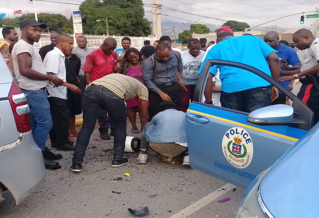 Police and civilians attend to an injured motorcyclist following a road accident in Dunrobin, St Andrew earlier this year.