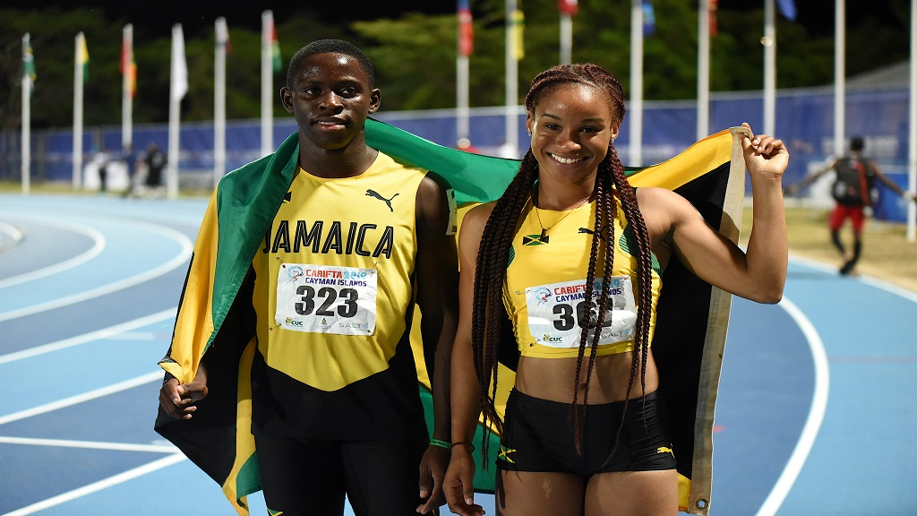 Oblique Seville (left) and Florida-based Briana Williams pose with the Jamaican flag after winning the Boys and Girls' Under-20 100m finals at the Carifta Games  in the Cayman Islands on Saturday, April 20, 2019.
