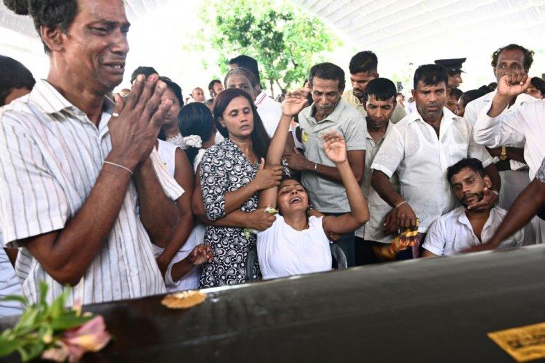 Des proches pleurent devant le cercueil d'une victime des attentats lors de funérailles à l'église Saint-Sébastien de Negombo au Sri Lanka, le 23 avril 2019