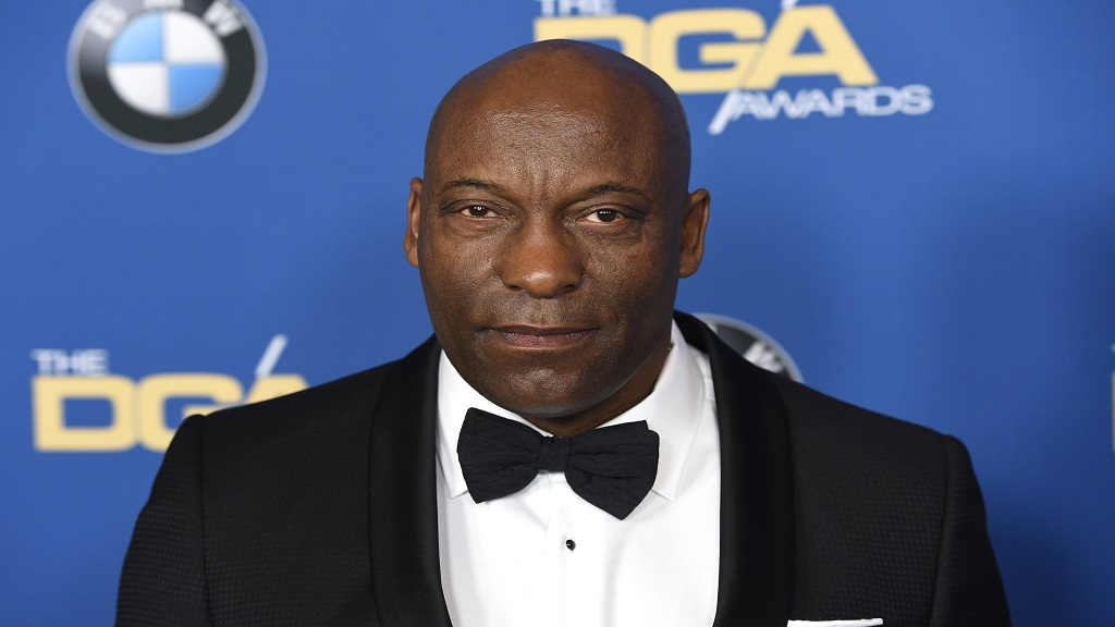 "FILE - In this Feb. 3, 2018 file photo, John Singleton arrives at the 70th annual Directors Guild of America Awards in Beverly Hills, Calif. The ""Boyz N the Hood"" director suffered a stroke last week and remains hospitalized, according to a statement from his family on Saturday, April 20, 2019. (Photo by Chris Pizzello/Invision/AP)"