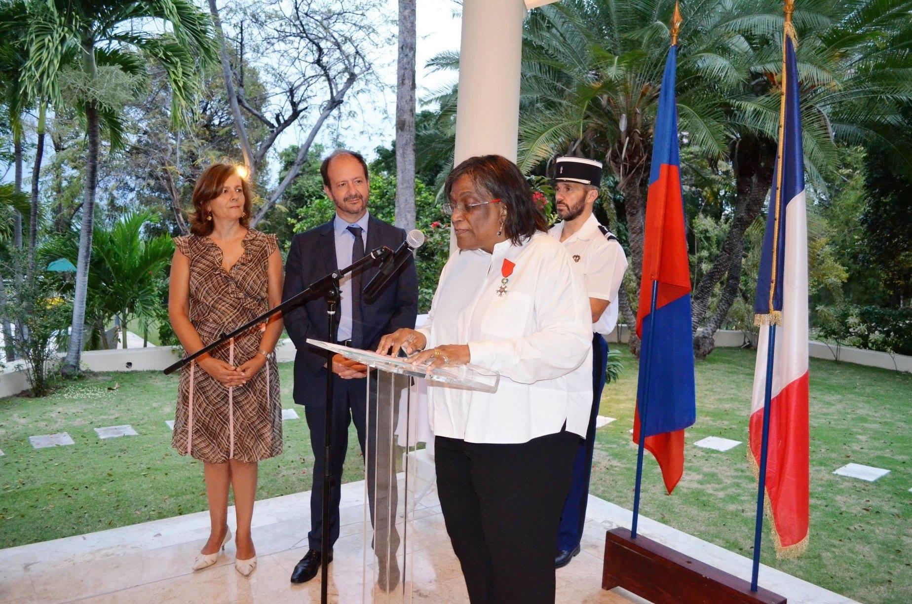 Michèle Oriol, décorée des insignes de Légion d'Honneur par l'ambassadeur français en Haiti, José Gomez./Photo: Ambassade de France.