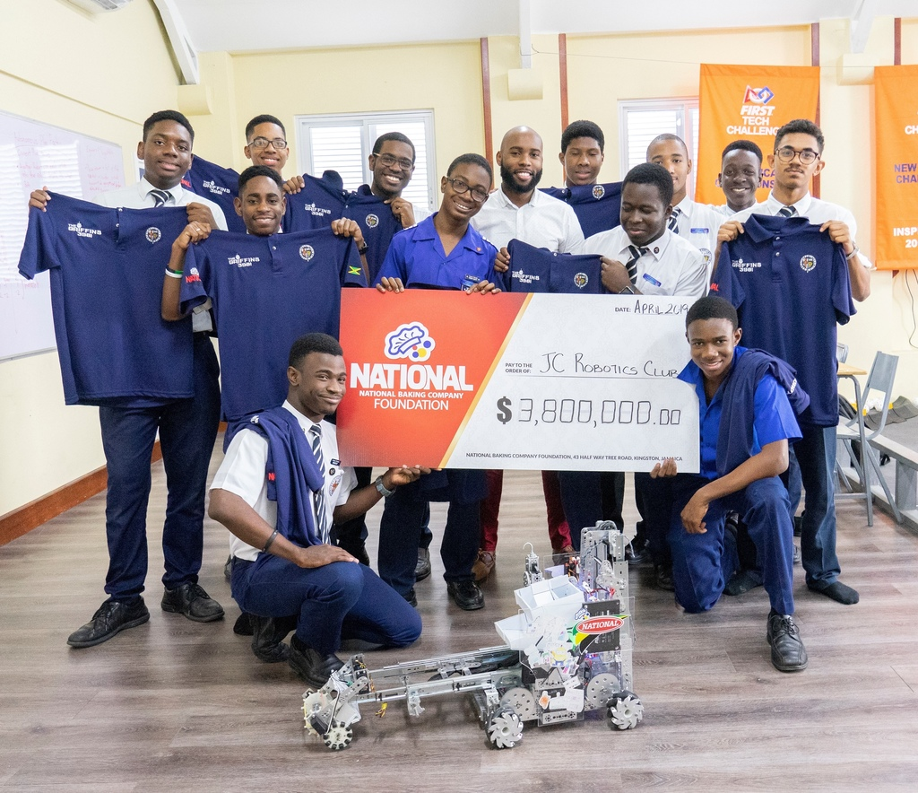 Members of the Jamaica College Robotics Club, Faculty Advisor, Jason Brown and their robot, Waffles pose with the cheque valued at $3.8 Million courtesy of The National Baking Company Foundation at the club's newly refurbished robotics lab at the Hope Road-based school.
