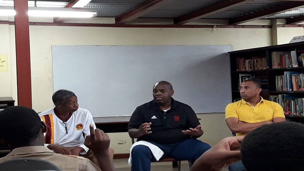 Accomplished basketball coach, Nicholas Davis (centre) makes a point in discussion with Wolmer's Boys' School students while Class of 1982 old boys Karyl Walker (left) and Craig Wellington look on.