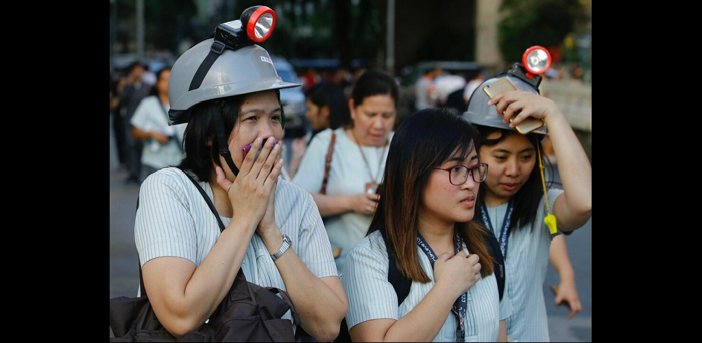 Wearing protective helmets, employees evacuate their office building following an earthquake in Manila, Philippines Monday, April 22, 2019.