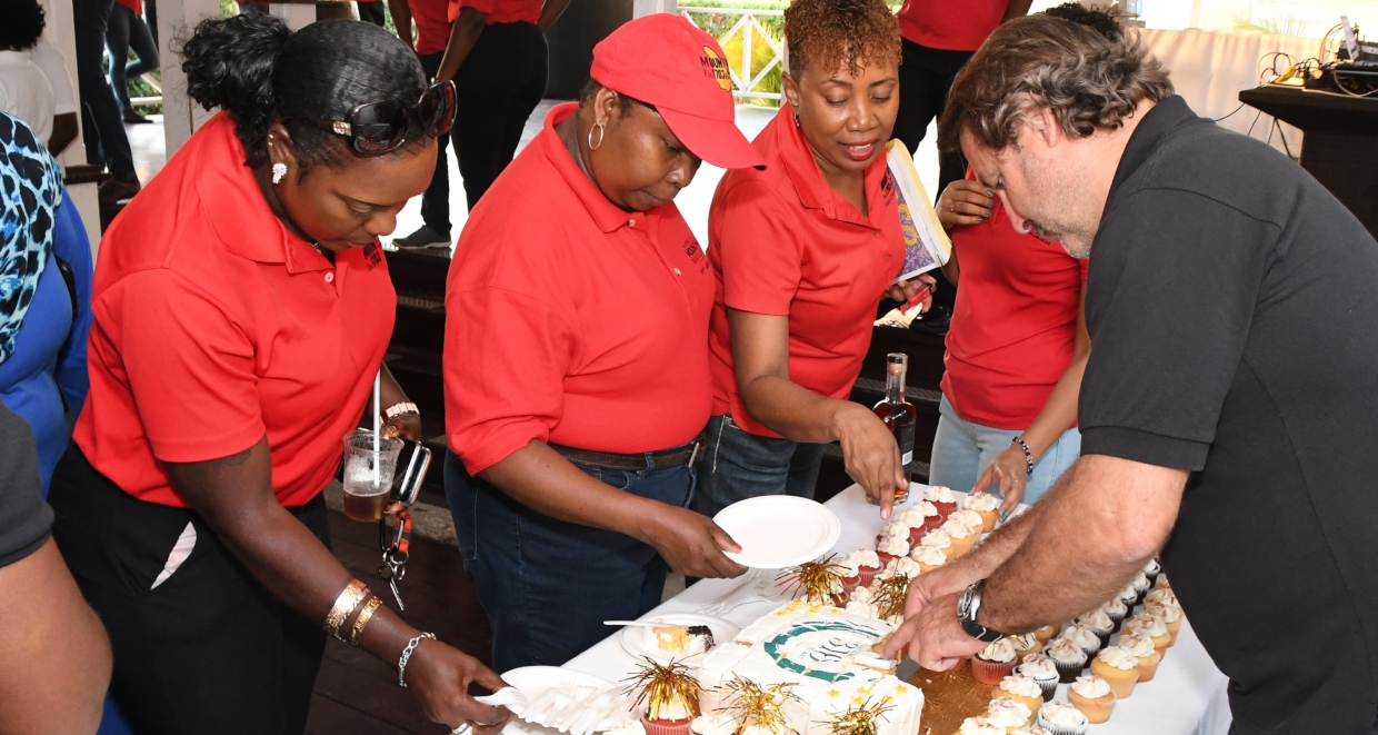 Mount Gay's Managing Director Raphael Grisoni (right) and staff members sharing the cake at the company's 316th anniversary staff celebration.