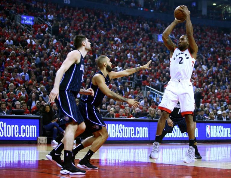 Kawhi Leonard (d) des Toronto Raptors tente un tir à 3 pts face aux joueurs d'Orlando en play-offs NBA, le 16 avril 2019 à Toronto