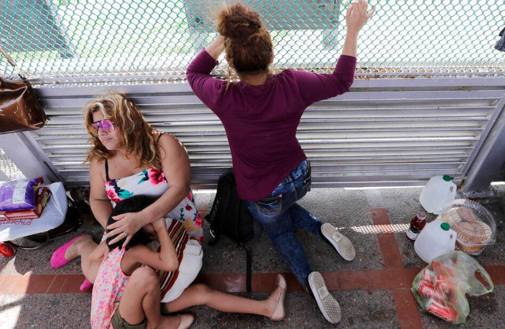 In this June 24, 2018, file photo, immigrants from Honduras seeking asylum wait on the Gateway International Bridge, which connects the United States and Mexico, in Matamoros, Mexico. (AP Photo/David J. Phillip, File)