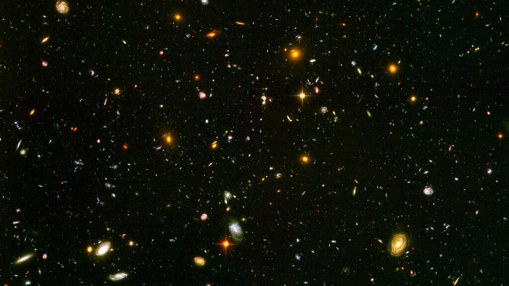 This image made from a composite of September 2003 - January 2004 photos captured by the NASA/ESA Hubble Space Telescope shows nearly 10,000 galaxies in the deepest visible-light image of the cosmos, cutting across billions of light-years. In research released on Friday, April 26, 2019, Nobel winning astronomer Adam Riess calculates the cosmos is between 12.5 and 13.0 billion years old - about 1 billion years younger than previous estimates. (NASA, ESA, S. Beckwith (STScI), HUDF Team via AP)
