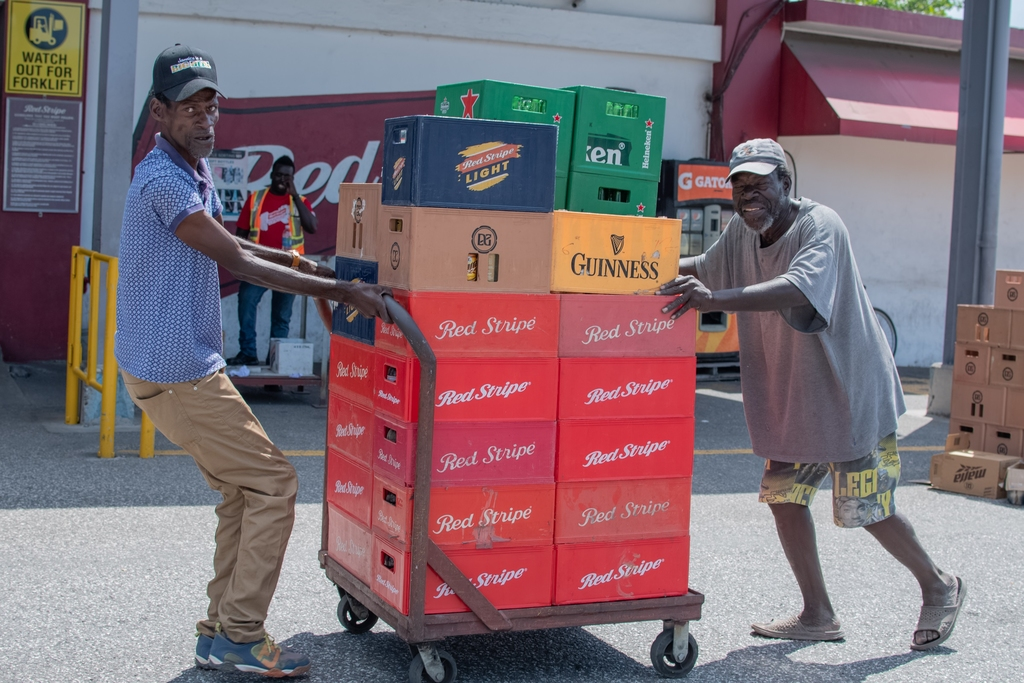 From left to right: Gardener, Joseph Hibbert and golf course caddy, Godfrey Bromwell bring a total of 120 crates of beer bottles to Red Stripe's 214 Exchange.