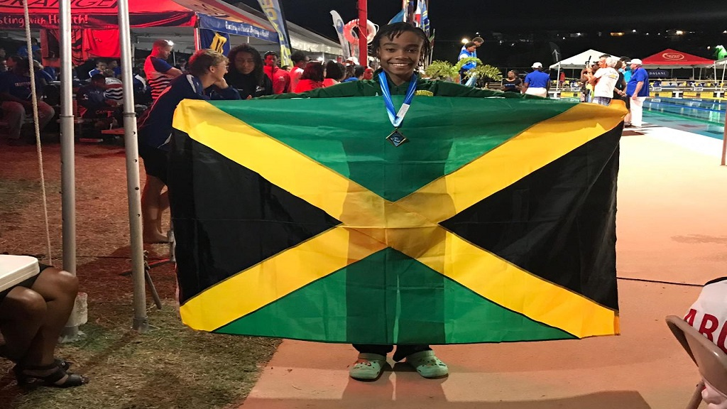 Zaneta Alvaranga celebrates with the Jamaican flag following her gold medal in the Girls' 13-14 50m butterfly final at the  Carifta Swimming Championships in Barbados on Sunday, April 21, 2019.