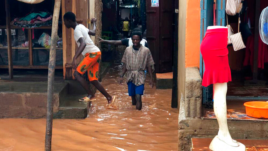 People walk through a flooded path leading to a shop during floods due to heavy rain in Pemba, Mozambique, Sunday , April 28, 2019. Serious flooding began on Sunday in parts of northern Mozambique that were hit by Cyclone Kenneth three days ago, with waters waist-high in areas, after the government urged many people to immediately seek higher ground. Hundreds of thousands of people were at risk. (AP Photo/Tsvangirayi Mukwazhi)