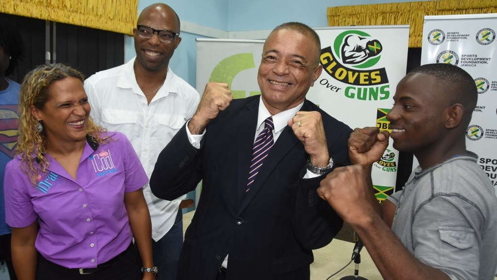 "Junior boxer Arnold Anderson (right) shows His Excellency Alexis Sandoval (centre), Ambassador of Panama to Jamaica how to set his guard at the launch of the Gloves over Guns community-based intervention programme. Looking on are Danielle Cunningham, beverage marketing manager, LASCO Distributors Limited and Stephen ""Bomber"" Jones, president of the Jamaica Boxing Board."