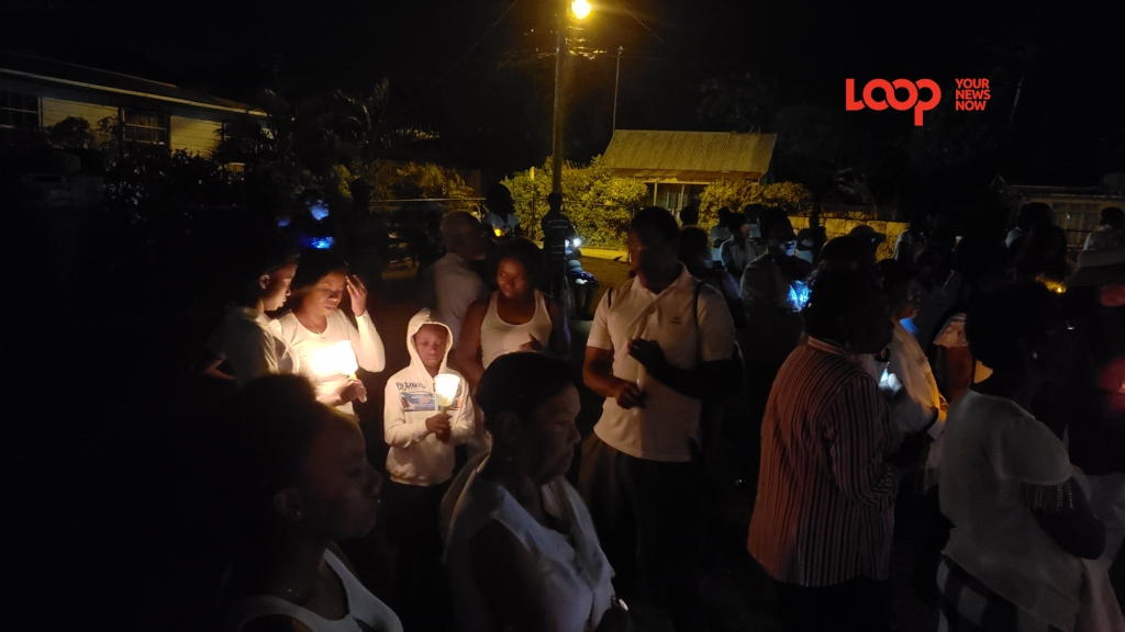 Candlelight vigil attendees were in a somber mood as they backed the home where two neighbours were gunned down three Sundays ago.