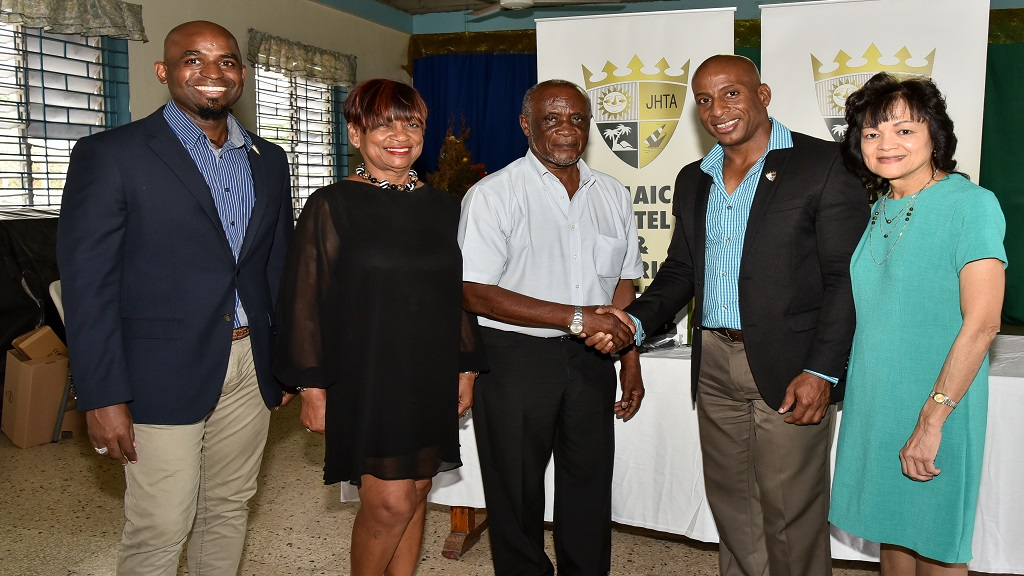 Winston Bowen (centre), Manager of the Maxfield Park Children's Home following the presentation of a computer to the Home by Jamaica Hotel & Tourist Association (JHTA) representatives (l-r) Robert Headley, 3rd Vice President; Vana Taylor, 1st Vice President; Omar Robinson, President and Camille Needham, Executive Director.