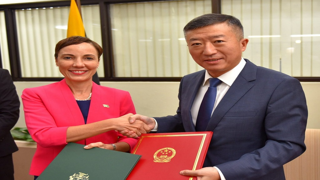 Minister of Foreign Affairs and Foreign Trade, Senator the Kamina Johnson Smith (left) and Chinese Ambassador to Jamaica, His Excellency Tian Qi (right), exchange the signed agreements under the Belt and Road Initiative (BRI), at the MInistry in New Kingston. (Photo via JIS)