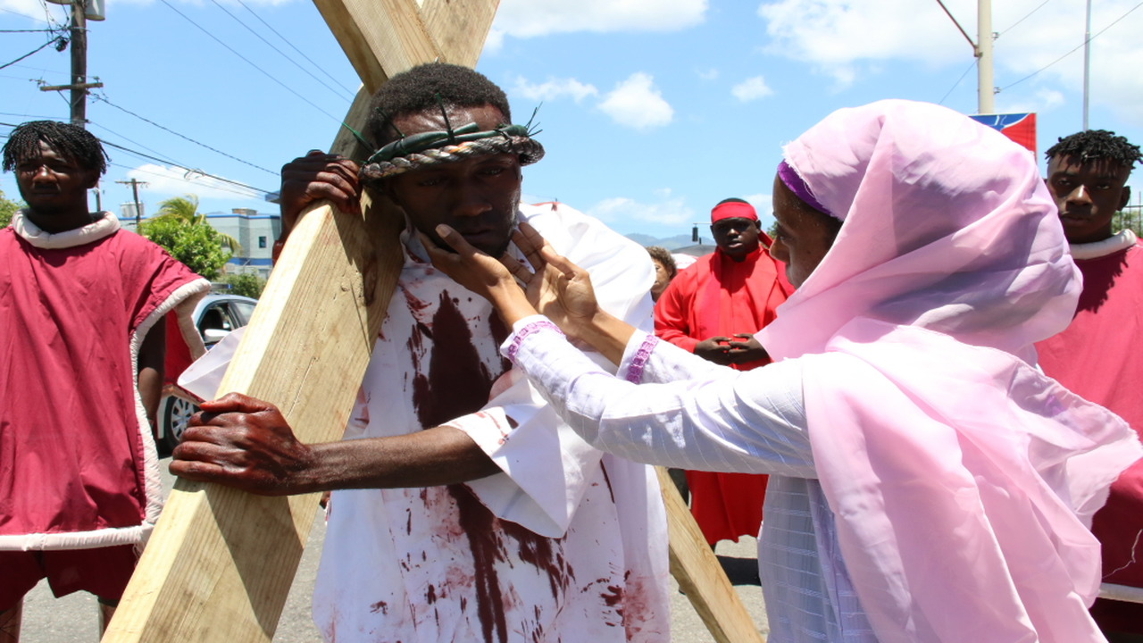 A 'mourner' attends to 'Jesus' during Holy Cross Roman Catholic Church's annual crucifixion re-enactment on Good Friday. (PHOTOS: Llewellyn Wynter)