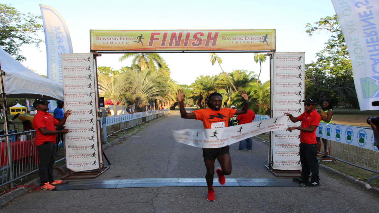 Kemar Leslie crosses the tape first in the 5K at the Everyone's A Winner/Running Events race series held at the Hope Botanical Gardens on Sunday. (PHOTO: Llewellyn Wynter)