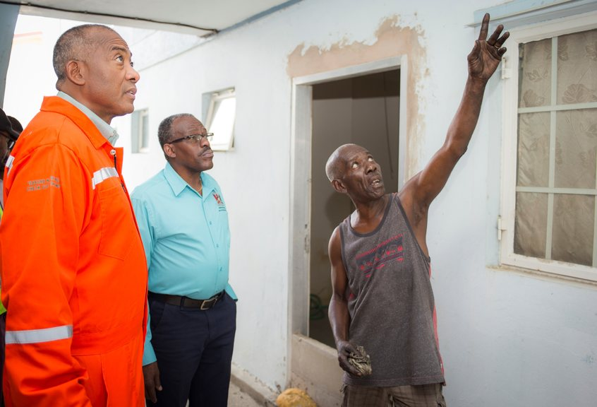 Housing and Urban Development Minister, Edmund Dillon and HDC Managing Director, Brent Lyons (right) examine some of the damages to the area outside a resident's apartment. Photo courtesy the Housing Development Corporation (HDC).