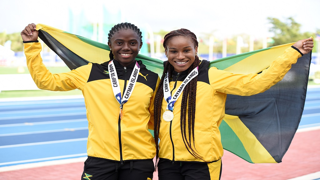 Briana Williams (right) and Joanne Reid celebrate with the Jamaican flag after a one-two finish in the Girls' Under-20 200m final at the Carifta Games in the Cayman Islands on Sunday, May 21, 2019. Williams won the event to complete the sprint double.