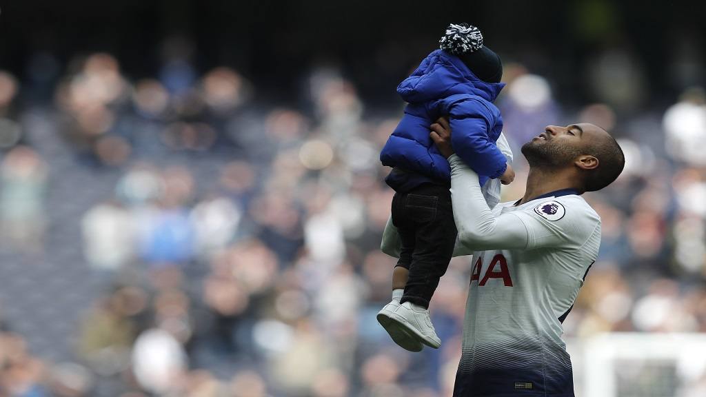 Tottenham's Lucas Moura celebrates with his son at the end of the English Premier League football match against Huddersfield Town at Tottenham Hotspur stadium in London, Saturday, April 13, 2019.