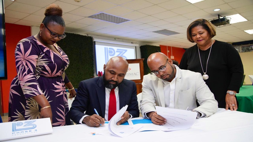 Dr Livingston White (seated left), Director, CARMAC, UWI and Delano Forbes, CEO, Phase 3 Production sign off on a 5-year Internship Scholarship MOU while Ms RaeAnn Smith (standing left), Film Production CARIMAC and Dr Marcia Forbes, Executive Chair of Phase 3 look on.