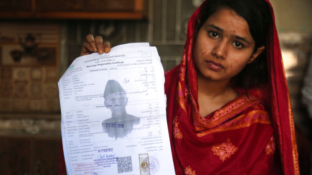 In this April 14, 2019 photo, Mahek Liaqat, who married a Chinese national, shows her marriage certificate in Gujranwala, Pakistan. (AP Photo/K.M. Chaudary)