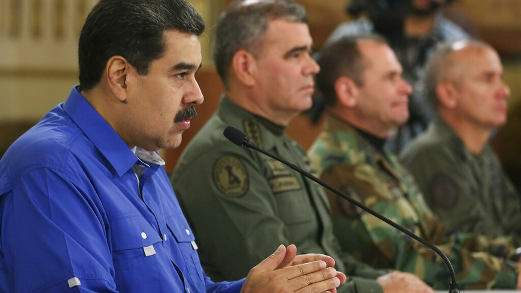 In this photo released by the Miraflores Press Office, Venezuela's President Nicolas Maduro, left, flanked by Venezuela's Defense Minister Gen. Vladimir Padrino Lopez, second left, Commander of Strategic Operations Adm. Remigio Ceballos, third from left, and Venezuela's Army Gen. Jose Ornelas, right, speaks during a televised national message at Miraflores Presidential Palace in Caracas, Venezuela, Tuesday, April 30, 2019. (Miraflores Press Office via AP)