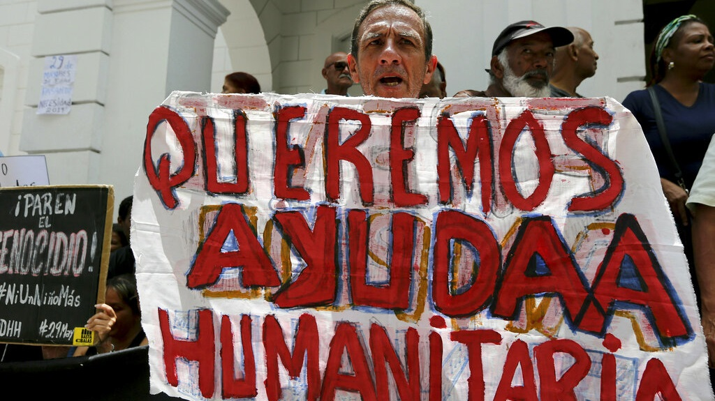 "A protester holds up the Spanish message ""We want Humanitarian Aid"" outside the Venezuelan Red Cross headquarters where demonstrators shouted slogans against Venezuelan President Nicolas Maduro in Caracas, Venezuela, Wednesday, May 29, 2019. Demonstrators protested the deaths of several children with leukemia who were awaiting bone marrow transplants, which has ignited a bitter dispute between the government and opponents over who is to blame. (AP Photo/Fernando Llano)"