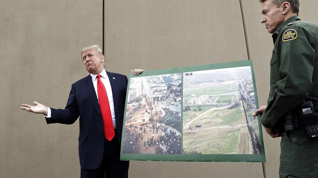 In this March 13, 2018, file photo, President Donald Trump holds a poster with photographs of the U.S. - Mexico border area as he reviews border wall prototypes in San Diego with Rodney Scott, the U.S. Border Patrol's San Diego sector chief. U.S. District Judge Haywood Gilliam Jr. has blocked President Donald Trump from building sections of his long-sought border wall with money secured under his declaration of a national emergency, Friday, May 24, 2019. (AP Photo/Evan Vucci, File)