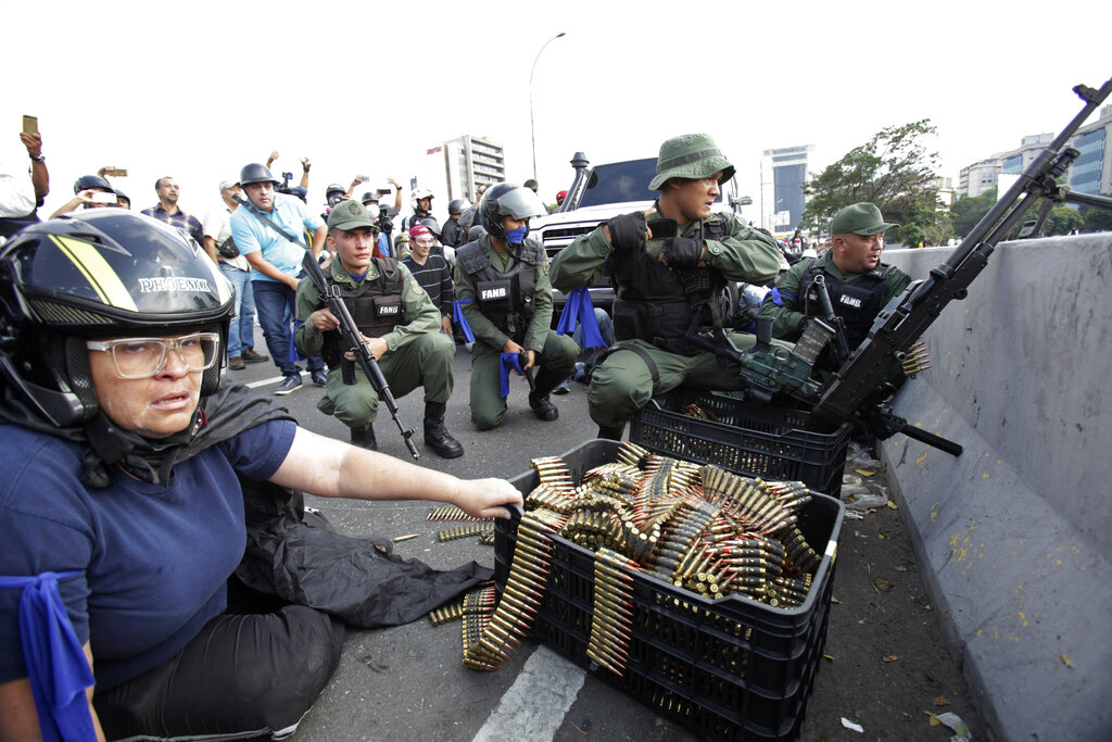 In this April 30, 2019 photo, an anti-government protester sits by ammunition being used by rebel troops rising up against the government of Venezuela's President Nicolas Maduro as they all take cover on an overpass outside La Carlota military airbase where the rebel soldiers confront loyal troops inside the base in Caracas, Venezuela. (AP Photo/Boris Vergara)