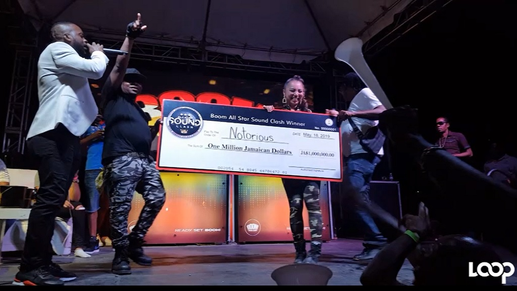 Likkle Shabba and Marie pose with the winning symbolic cheque following their victory in the Boom All-Star Sound Clash.