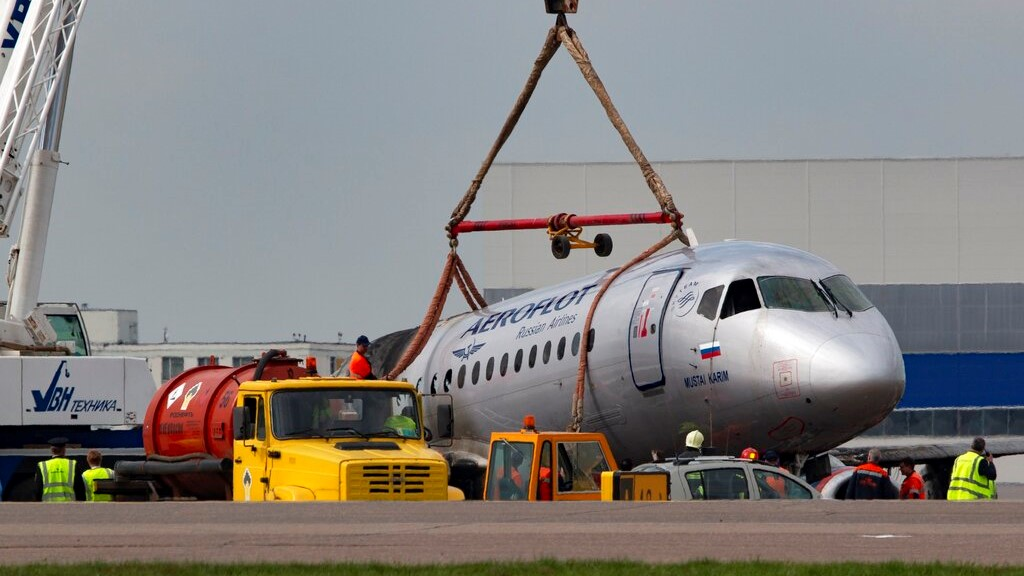 A crane lifts the damaged Sukhoi SSJ100 aircraft of Aeroflot Airlines in Sheremetyevo airport, outside Moscow, Russia, Monday, May 6, 2019. (AP Photo)