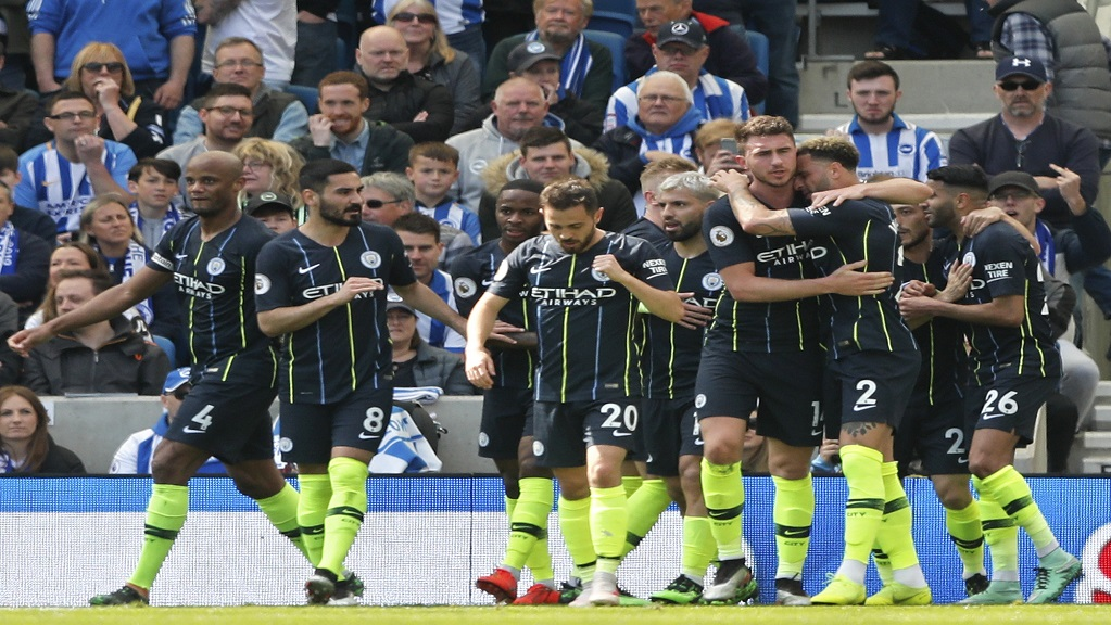 Manchester City's Aymeric Laporte is hugged by teammate Kyle Walker, foreground right, after scoring his side's second goal during the English Premier League football match between Brighton and Manchester City at the AMEX Stadium in Brighton, England, Sunday, May 12, 2019. (AP Photo/Frank Augstein)